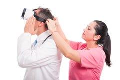Infirmière féminine ajustant des verres de vr au docteur masculin images stock