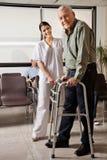 Infirmière féminine Helping Senior Patient avec le marcheur Images libres de droits