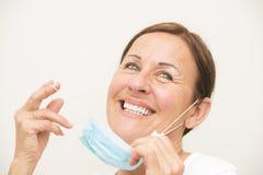 Infirmière féminine heureuse avec le masque sur le blanc Photographie stock libre de droits
