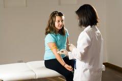 Infirmière féminine préparant un bras de filles pour la vaccination Photographie stock