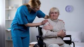 Infirmi?re f?minine prenant soin de fauteuil roulant se reposant de patient plus ?g?, service hospitalier photographie stock libre de droits