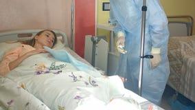 Infirmière féminine vérifiant le compte-gouttes avec le médicament, rendant des premiers secours au patient photo libre de droits