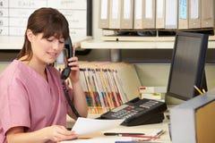 Infirmière faisant l'appel téléphonique à la gare d'infirmières Photos libres de droits