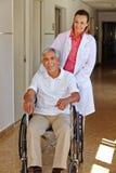 Infirmière gériatrique avec l'homme supérieur dans le fauteuil roulant Photographie stock