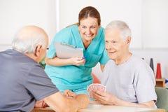 Infirmière gériatrique observant de vieux hommes playying des cartes Image stock