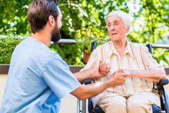 Infirmière gériatrique tenant la main de dame âgée dans la maison de repos Image stock