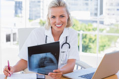 Infirmière gaie tenant un rayon de x dans son bureau Photos stock