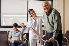 Infirmière Helping Senior Patient avec le marcheur Images stock