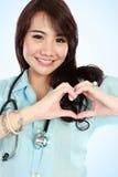 Infirmière heureuse de jeunes avec des mains de forme de coeur Images libres de droits