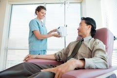 Infirmière Looking At Patient tout en ajustant IV Photographie stock libre de droits