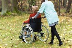 Infirmière marchant avec la dame handicapée Photographie stock libre de droits