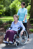 Infirmière marchant avec la dame handicapée Images stock