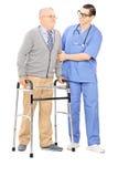 Infirmière masculine aidant un homme supérieur avec le marcheur Photos stock
