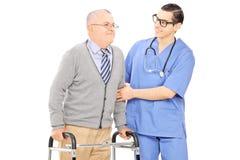 Infirmière masculine aidant un homme supérieur avec le marcheur Photographie stock libre de droits