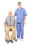 Infirmière masculine et un aîné dans la pose de fauteuil roulant Photos stock