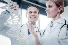 Infirmière mignonne stupéfaite tenant et regardant le modèle d'ADN Images libres de droits
