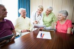 Infirmière montrant à aînés quelque chose Photographie stock libre de droits