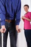 Infirmière observant l'homme handicapé sur des béquilles Images libres de droits
