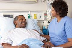 Infirmière parlant au patient mâle supérieur sur la salle photo stock