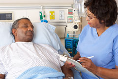 Infirmière parlant au patient mâle supérieur sur la salle photographie stock