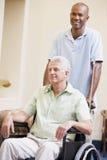 Infirmière poussant l'homme dans le fauteuil roulant Photo stock