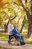 Infirmière poussant l'homme supérieur dans le fauteuil roulant Image libre de droits
