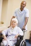 Infirmière poussant le femme aîné dans le fauteuil roulant Photographie stock