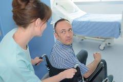 Infirmière poussant le patient sur le fauteuil roulant Photos libres de droits