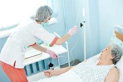 Infirmière préparant le compte-gouttes pour l'injection intraveineuse photo stock