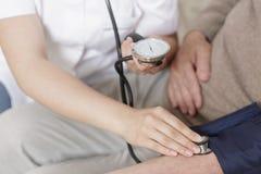 Infirmière prenant la tension artérielle image stock