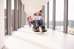 Infirmière Pushing Senior Patient dans le fauteuil roulant le long du couloir photographie stock libre de droits