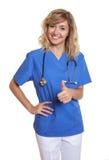 Infirmière riante montrant le pouce Photo stock