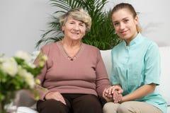 Infirmière s'inquiétant d'une femme plus âgée Image stock