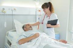 Infirmière salut le patient mûr dans la chambre d'hôpital Photographie stock