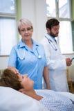 Infirmière vérifiant la température patiente Image libre de droits