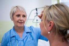 Infirmière vérifiant la température patiente images libres de droits