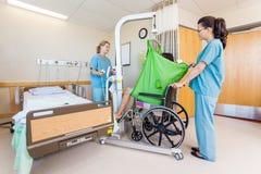 Infirmières de femelle transférant le patient à partir d'hydraulique photos stock