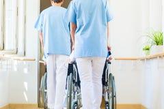 Infirmières poussant des aînés dans le fauteuil roulant par la maison de repos Image libre de droits