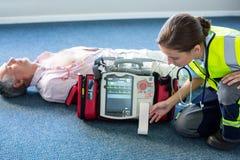 Infirmier à l'aide d'un défibrillateur externe pendant la réanimation cardio-respiratoire Photographie stock libre de droits