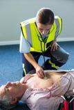 Infirmier examinant un patient pendant la réanimation cardio-respiratoire Images stock