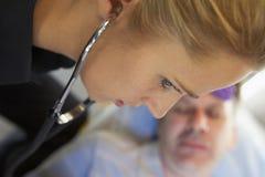 Infirmier à l'aide du stéthoscope sur le patient Image libre de droits