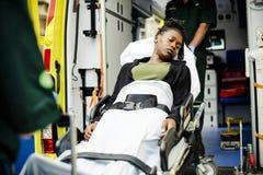 Infirmiers entrant un patient sur une civière dans une ambulance photographie stock
