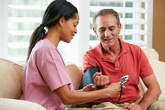 Infirmière rendant visite au patient mâle supérieur à la maison Photos stock