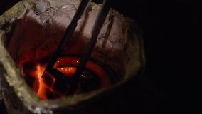 Inflammation en gros plan du charbon carré pour un narguilé avec une spirale chaude banque de vidéos