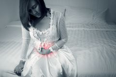 Inflammatory Bowel Disease or Ulcerative colitis. Asian woman in white satin nightgown have a stomachache in bedroom cause Ulcerative Colitis at night stock image