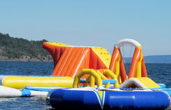Inflatable aquapark attractions in water. Inflatable attractions on the water. Floating entertainment for children having fun swimming in lake or sea water stock photography