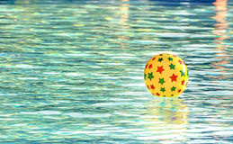 Inflatable ball floating in swimming pool Royalty Free Stock Photos