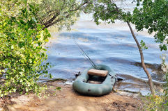 Inflatable boat on the bank of the lake. Rods and other fishing Stock Images