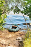 Inflatable boat on the bank of the lake. Rods and other fishing Royalty Free Stock Photo
