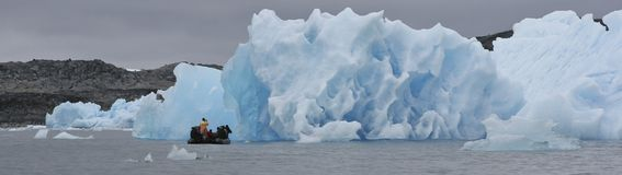 Inflatable boat and iceberg. Close up of iceberg in Napassorsuaq Fjord with inflatable boat in foreground, Greenland Royalty Free Stock Image